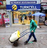 KADIKOY, TURKEY - SUNDAY, MARCH 9, 2014: A pedestrian walks past an Turkcell mobile telephone retail
