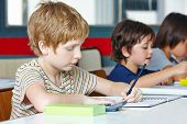 Lefthanded boy in elementary school writing with a pencil