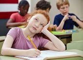 Pensive girl in elementary school class thinking and writing
