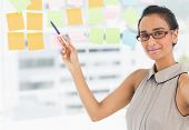Designer pointing to sticky notes on window smiling at camera in creative office