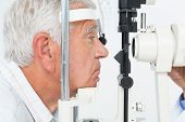 Close-up side view of a senior man getting his cornea checked