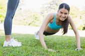 Portrait of smiling woman doing push ups in park with friend standing by her