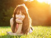 Young, beautiful, natural woman lying on the grass at summer sunset, portrait. Happiness, fun and harmony