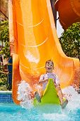 Child on water slide at aquapark. Summer holiday.