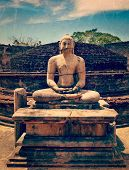 Vintage retro hipster style travel image of ancient sitting Buddha image in votadage with grunge tex