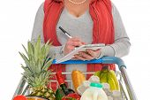 A woman checking her shopping list with a trolley full of fresh food, isolated on a white background.
