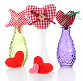 Hand-made textile hearts in different vases, isolated on white