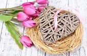 Decorative heart in nest, on color wooden background
