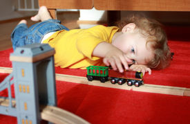 foto of track home  - Child toddler boy playing at home with trains and tracks - JPG