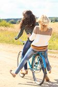Two girls ride bicycles on road