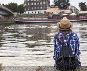 Young girl (rear view) sits on the bank of Vistula River in Krakow. European Tour.