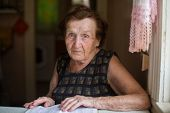 Worried elderly woman sitting at table in the house.
