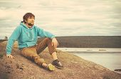 Young Man Hipster Relaxing Alone Outdoor With Mountains And Lake On Background Lifestyle Concept