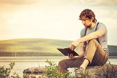 stock photo of swag  - Young Man reading book outdoor with lake on background Summer vacations and Lifestyle concept