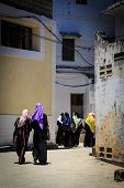 Veiled Women Walking Through A City Street