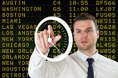 Young serious businessman pointing to a white clock against black airport departures board for ameri