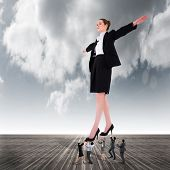 Composite image of business team supporting boss against cloudy sky background