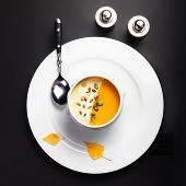 Pumpkin Soup With Cream And Pumpkin Seeds In A White Bowl Over Black Background