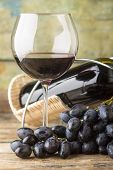 Cluster Of Fresh Dark Blue Grapes With Red Wine In Glass On Wood Background