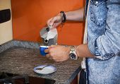 Male hands in home kitchen pouring espresso coffee from coffee-maker