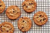 Freshly baked oatmeal raisin cookies on cooling rack over rustic wood background. Closeup from above