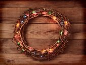High angle view of a wicker Christmas wreath with holiday lights, on a rustic wooden surface. Square