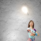 Young woman in colorful dress looking at light bulb