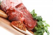 raw meat : fresh beef pork big rib and fillet with garlic and green stuff on wood isolated over whit