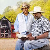 A mature African American cowboy couple reading the Bible in an old western town.
