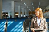 Serious businesswoman with touchpad sitting in airport