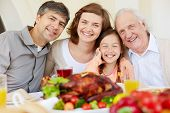 Portrait of happy family looking at camera by Thanksgiving table