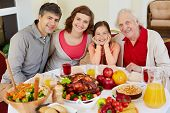 Portrait of happy family sitting at festive table on Thanksgiving day