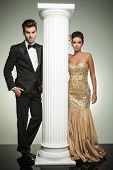 luxury couple posing in studio near column, ceremony concept
