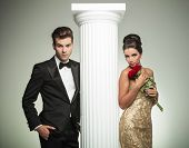 elegant young couple posing near column, woman is holding roses