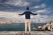 Asian man open arms and looking the skyline of the city, Kaohsiung, Taiwan, Asia.