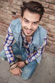 Attractive casual man posing against a brick wall, holding his hands on the wall, looking at the cam