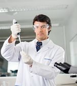 Mid adult male scientist filling solution into test tube in medical lab