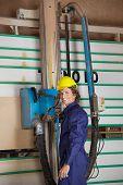 Portrait of confident carpenter using vertical saw machine in workshop