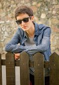 Hipster teenager with sunglasses over a fence
