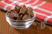 bowl of chocolate pieces on wooden table