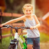 happy little girl with her bicycle in rural areas close-up