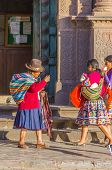 CUZCO, PERU, MAY 1, 2014 - Two girls in folk costumes walk carrying llama babies while souvenir seller greets them.