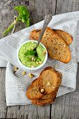 image of peas  - Green pea hummus with pine nuts and thin croutons on wooden table with linen napkin