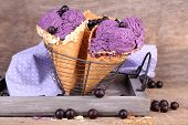Tasty ice cream with berries in waffle cones on brown wooden background