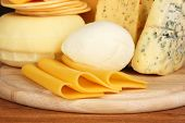 Various types of cheese on wooden board close up