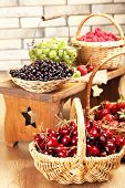 Fresh berries in basket on wall background