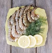 Plate of prawns with dill and lemon on grey wooden background