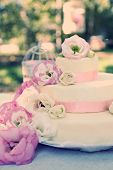 Beautiful wedding cake with flowers on table, outdoors