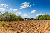 plowed field on a background of rural houses