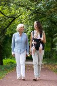 Mother Walking Outdoors With Grandmother And Baby